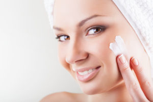 Close-up beautiful woman applying moisturizer cosmetic cream on face on light background