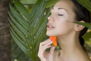 Beautiful caucasian woman having fresh papaya natural facial mask apply skin care and wellness. Fresh papaya fruit. Facial mask of papaya slices at spa salon