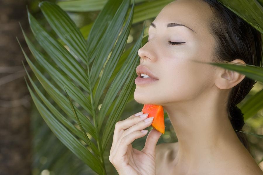Beautiful caucasian woman having fresh papaya natural facial mask apply skin care and wellness. Fresh papaya fruit. Facial mask of papaya slices at spa salon
